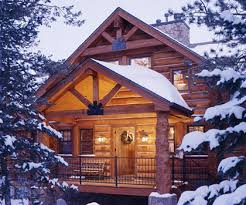 log home designers. colorado mountain log home tour: front entry of snow covered cabin. designers