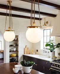 bright kitchen lighting. old world brass globe pendants and black kitchen cabinets with hardware lacanche range bright lighting