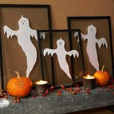 Halloween decorating ideas emphasized with light. white ghosts in black  frames and candles for fireplace decorating