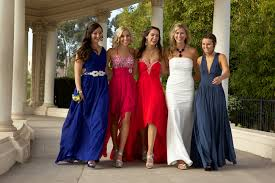 friends posing for a photograph in their prom dresses