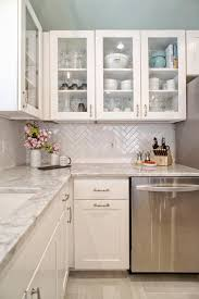 Diagonal subway tile backsplash, stainless steel appliances, marble  countertops, and white cabinets with