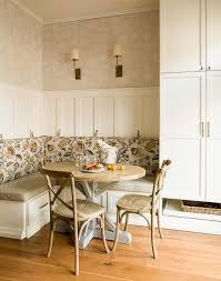 Cottage breakfast nook features an L shaped built-in banquette with storage  drawers adorned with