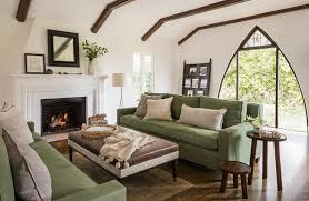 stunning green and brown mediterranean living room is furnished with a brown leather ottoman placed on a gold persian rug between facing green sofas topped