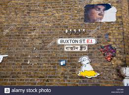 graffiti or street art on wall with street name sign and equivalent in bengali buxton street off brick lane london e1 uk on wall art street names with graffiti or street art on wall with street name sign and equivalent