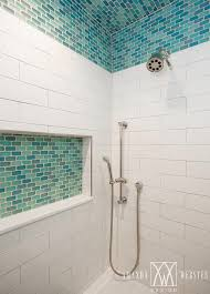 gorgeous blue and white walk in shower is clad in turquoise blue glass ceiling tiles that continue down to frame white brick shower tiles fitted with a