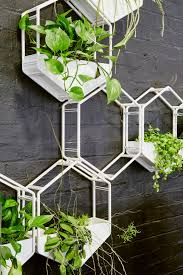 close up of white wabe cer with plants and planter baskets