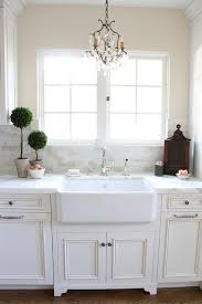 fabulous kitchen features white cabinets accented with raised panel doors paired with statuary marble counters and a white mini brick marble tiled