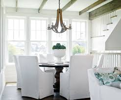 beach style dining room features a shiplap ceiling accented with rustic wood beams accented with a wood chandelier arteriors manning chandelier