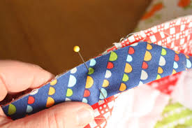 How to Finish and Bind a Quilt - Diary of a Quilter - a quilt blog & Pin the raw edges (non-folded-edge) to the raw outside edges of the quilt  front. This is personal preference, but I then like to pin the entire  binding to ... Adamdwight.com