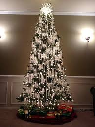 Green tree with only crystal ornaments.green tree with red bows and gold  ball ornaments with gold ting ting.white tree with retro ornaments and  lights