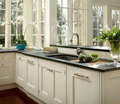 a kitchen with white cabinets and a black counter