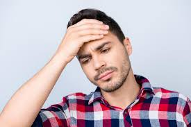 man with headache on top of head holding forehead in pain