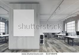 pictures of an office. front view of an office with a poster hanging on gray wall rows pictures