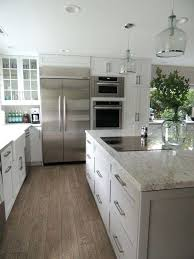 white kitchen cabinets with white and gray granite white kitchen with light wood floors and solid