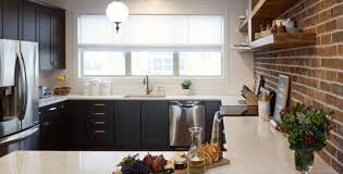 black shaker style cabinets mix with quartz countertops and an exposed brick wall for an