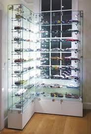 custom made l shaped glass display cabinet to exhibit model racing cars on adjule glass shelves with integral low voltage lighting