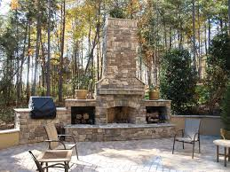 tiny chairs and square table on usual floortile near outdoor stone fireplace between logponds
