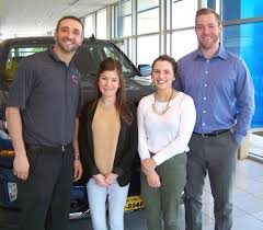 second from left and united way caign istant kalyn du second from right meet with rich burritt of burritt motors left and kevin dorsey of