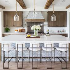 five white modern counter stools sit at an expansive gray mosaic tiled center island accented with a thick white marble countertop fitted with a stainless