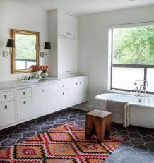 dark gray hexagonal floor tiles with nice orange colorful bath rugs using gold framed mirror