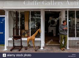 A Man Stands Outside An Antiques Shop Texting On A Smart Phone, High Street,