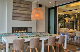 linear outdoor fireplace with tile and wood surround at mendocino farms in san go california