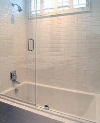 clean crisp white bathroom with white beveled subway tiles shower surround glass sliding shower doors and polished nickel shower kit