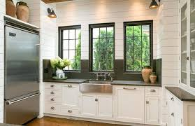 small u shaped kitchen with white cabinets with glass doors and slate countertops and backsplash