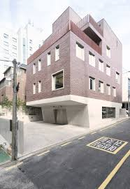 top heavy block in seoul features red brick top and concrete base bespoke brickwork garage office