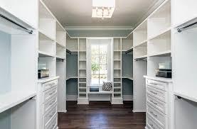 walk in closet with custom window seat shoe rack and drawers