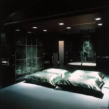 bedroom with black pillows and bedding dark green marble tiles on walls and white bath in background