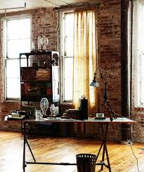 Bare brick wall, natural wood floors, and a vintage desk make this space an