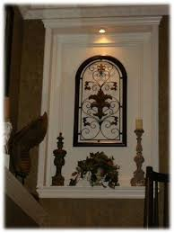 wall niche lighting. inset wall niche light on top with metal art and candles lighting