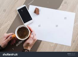 chocolate phone white. hands with cup of coffee, chocolate, phone and white paper chocolate