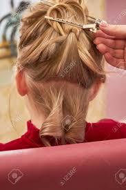 子供のクローズ アップの髪型美容師及び髪留めの手 の写真素材画像