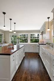 i like the bo of the butcher block and the other slab countertops plus the all white kitchen the rustic dark wood floors