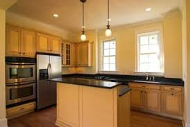 Creamy Yellow Walls Blend With Maple Cabinets Black Granite Counters And Mediumtoned Floors  T