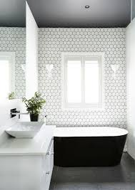 dark grey floors a dark ceiling and white hex tiles with black grout to tie