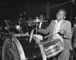 Judging from this young man's clothes, I'd guess that this photo is from  the 1940s, but the drum kit is pretty old school. One thing you'll note  from this ...