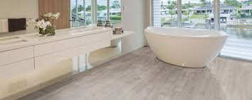 inspiring waterproof laminate flooring for modern bathroom that have big bathtub and white long wood bathroom cabinet with flower vase and towel holder rack