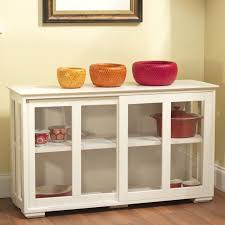 white lacquer wooden kitchen storage cabinet with sliding glass door placed on unpolished hardwood floor pantry
