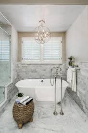 a metal orb chandelier is centered above the freestanding tub in within proportions 966 x 1449