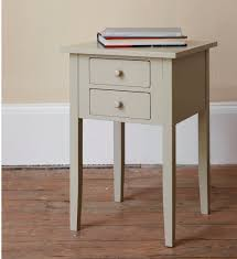 furniture white wooden bedside table with double drawers and four legs on wooden floor