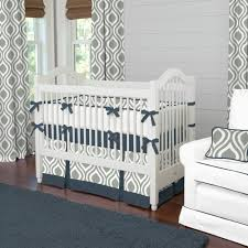 white wooden crib with white blue bedding plus gray white on the bottom side placed on