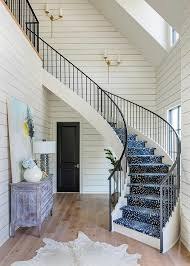 mount on a white shiplap wall along a two story foyer showcasing a winding staircase with wrought iron railing and a blue antelope pattern runner