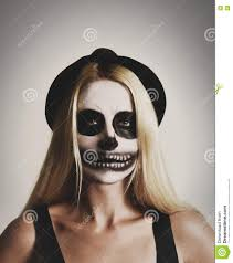 a young woman is wearing a y skeleton makeup mask with black and white paint on an background for a costume or fear concept
