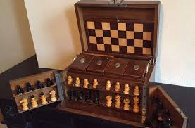a chess set in a wooden box with a card game and checker pieces