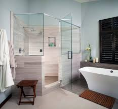 corner showers with glass shower door and tile flooring also tile showers and freestanding bathtub with blue walls plus wood bench and wood bath mat with