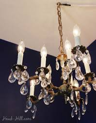 chandelier hung from a ceiling hook in an apartment with swagged cord