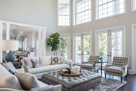 transitional living room in a two story home featuring a large gray leather tufted ottoman as a coffee table surrounding white linen slipcovered sofas and